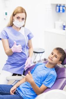 Dentista de sexo femenino joven y muchacho que gesticulan los pulgares para arriba en clínica