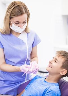 Dentista de sexo femenino que comprueba los dientes del muchacho feliz en clínica