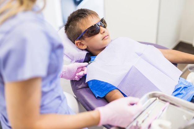 Dentista de sexo femenino que examina los dientes de un paciente en clínica