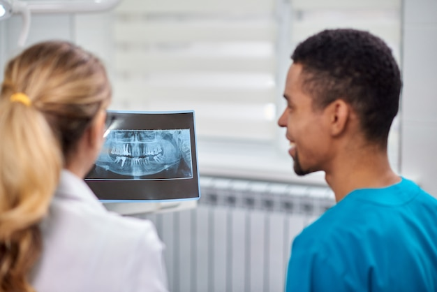 Dentista de sexo femenino que explica la radiografía al varón africano