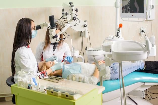 Dentista de sexo femenino que trata la caries usando el microscopio en la oficina del dentista