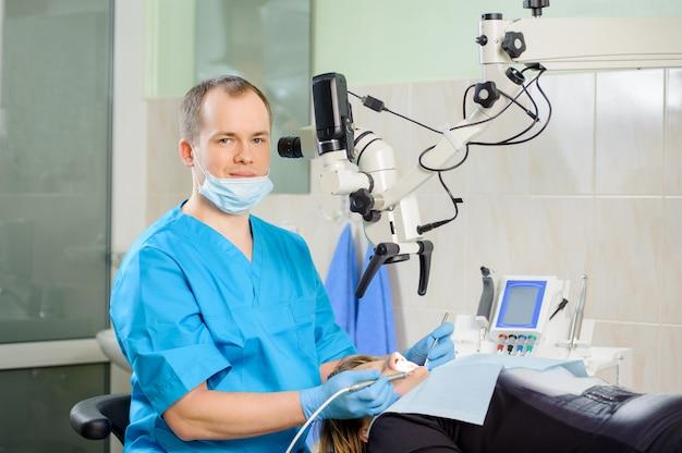 Dentista de sexo masculino que trabaja con el microscopio en la clínica moderna del dentista