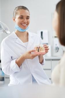 Dentista sonriente con modelo de diente