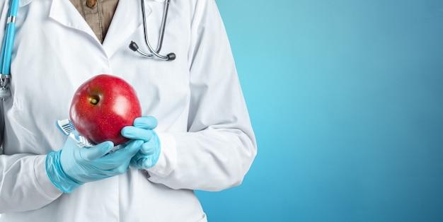 Dentista sosteniendo una manzana madura