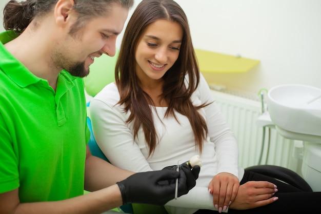 El dentista trata los dientes al cliente en la clínica dental