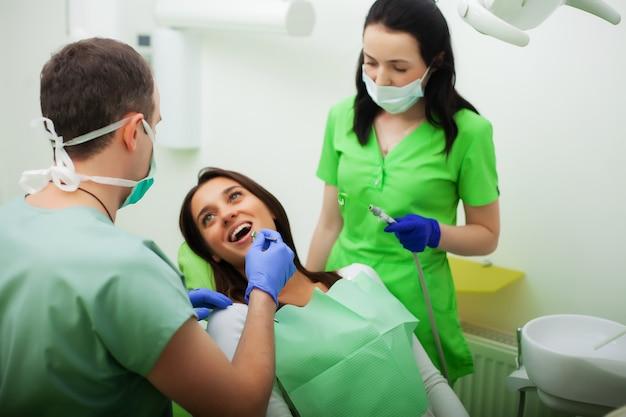 El dentista trata los dientes al cliente en el consultorio dental