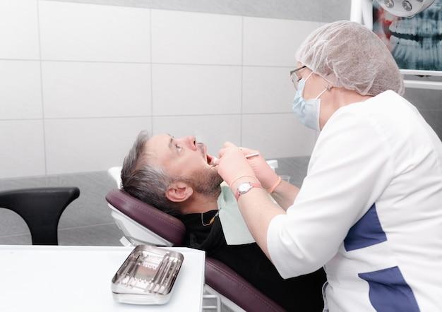 Una dentista trata los dientes de un paciente masculino en una moderna oficina de una clínica dental