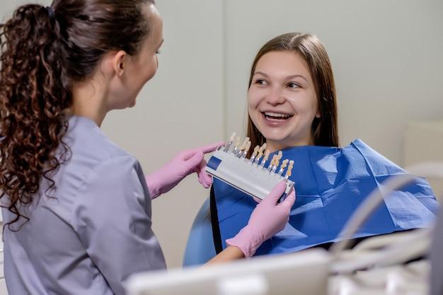 El dentista está tratando de elegir el color adecuado para los implantes dentales de la bella mujer.