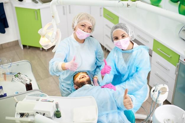 Dentistas felices y sonrientes y su cliente masculino mostrando todos los pulgares hacia arriba mientras un tratamiento dental exitoso en un consultorio dental.