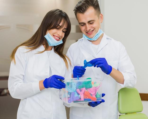 Dentistas sonriendo y sosteniendo la caja de retenedores