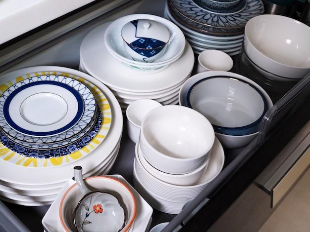Dentro de cajones de madera llenos de platos de cerámica blanca o plato y vajilla, tazón para comer, espacio interior de cocina en casa.