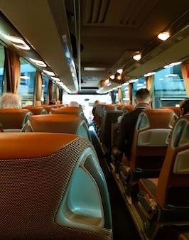 Dentro del gran bus turístico con gente.