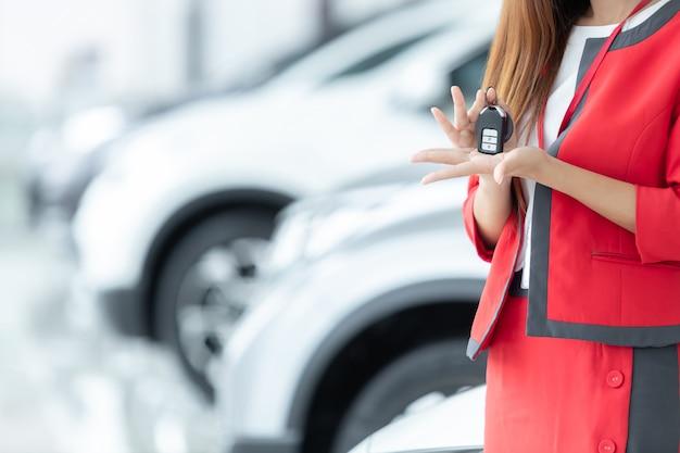 Dependienta asiática que da llave del coche sobre el fondo de la demostración auto, negocio auto, venta del coche.
