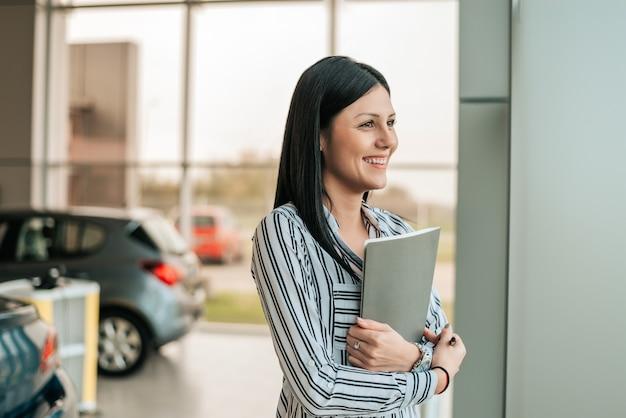Dependienta joven del coche que sostiene el tablero en la sala de exposición.