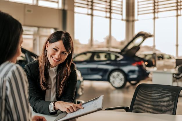 Dependienta sonriente del coche que discute un contrato con un cliente femenino.