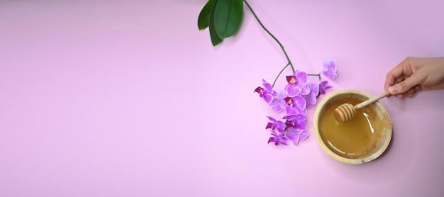 Depilación depilatoria pasta derretida, orquídea y mano femenina