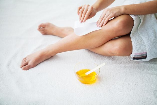 Depilación. piernas depilatorias con cera y cinta adhesiva.