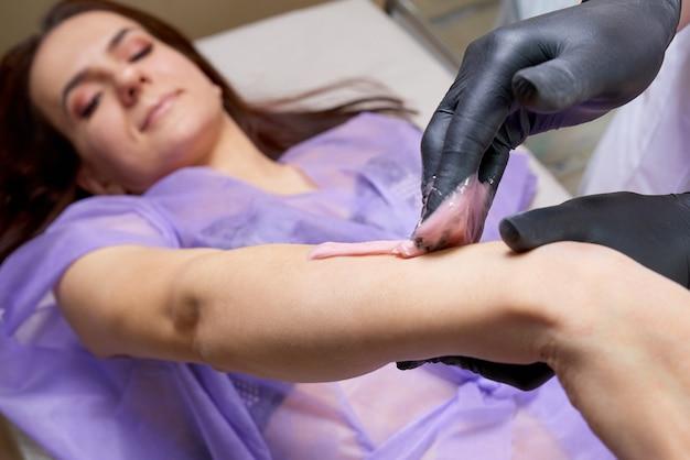 Depilación en salón de belleza por profesional. trabajador de salón de belleza aplicando cera y cinta para eliminar el vello de los brazos