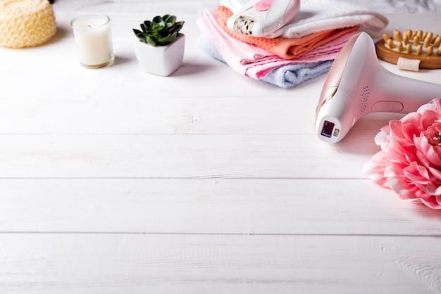 Depiladora láser moderna con accesorios de baño en el fondo blanco.