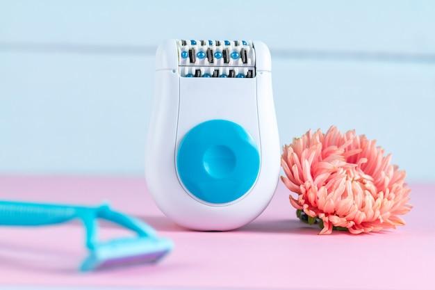 Depiladora, maquinilla de afeitar para mujer y una flor rosa. depilatorio. eliminación de vello no deseado.