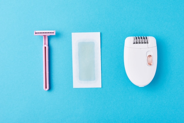 Depiladora, maquinilla de afeitar y tiras de cera en azul