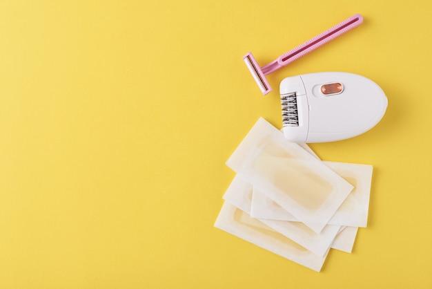 Depiladora, maquinilla de afeitar y tiras de cera sobre superficie amarilla