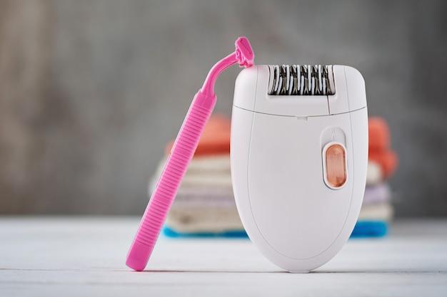 Depiladora, navaja de afeitar y toalla de baño.