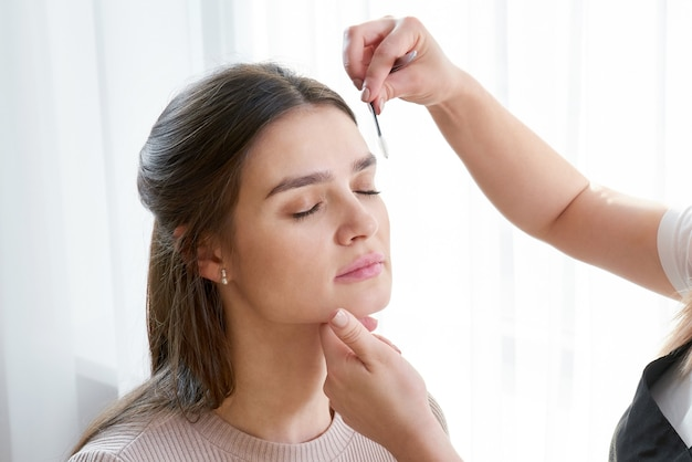 Depilarse las cejas femeninas con pinzas durante la corrección de cejas en un salón de belleza