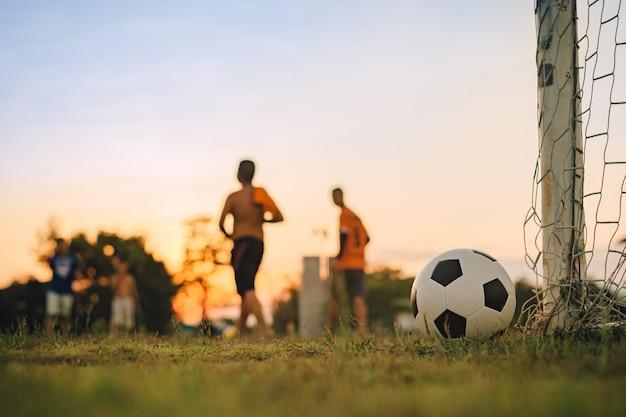 Deporte de acción al aire libre de diversidad de niños jugando fútbol soccer para hacer ejercicio