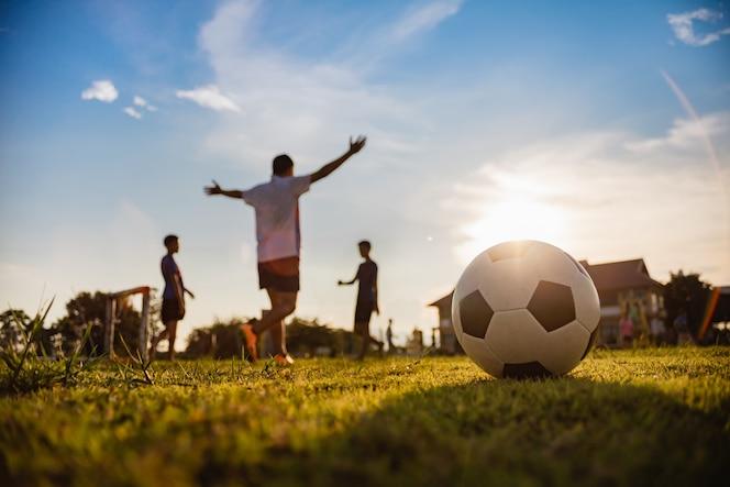 Deporte de acción al aire libre de niños que se divierten jugando al fútbol para hacer ejercicio.