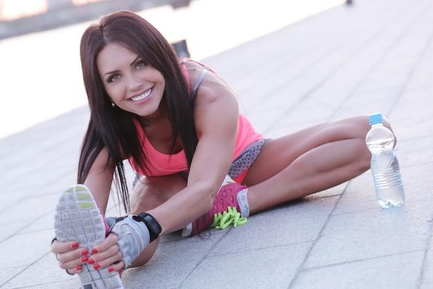 Deporte al aire libre, mujer estirando