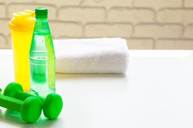 Deporte, estilo de vida saludable y concepto de objetos - cerca de pesas, botella de agua
