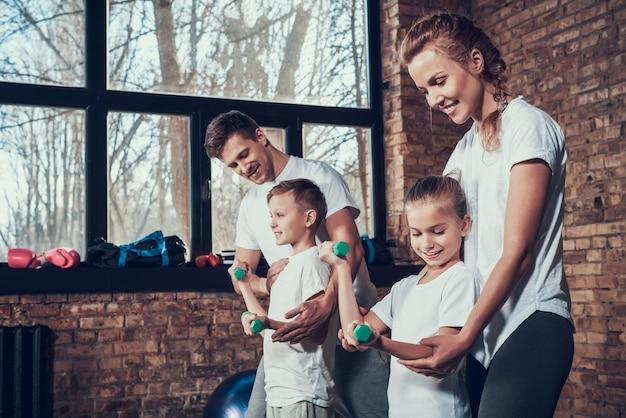 Deporte familia haciendo ejercicios con pesas.