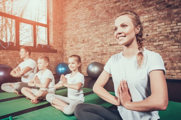 Deporte familia tener entrenamiento de yoga en el gimnasio.