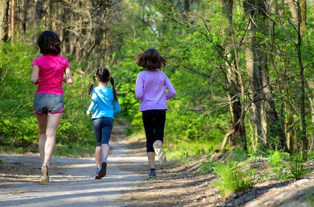 Deporte familiar, feliz madre activa y niños corriendo al aire libre, corriendo en el bosque