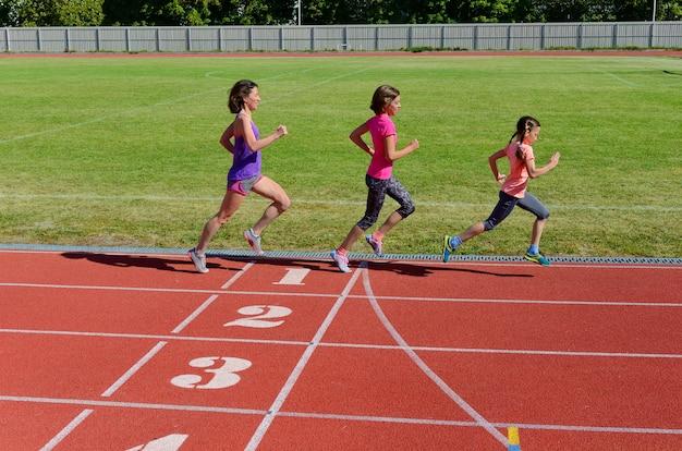 Deporte familiar y fitness, madre feliz y niños corriendo en la pista del estadio al aire libre, concepto de estilo de vida saludable y activo para niños