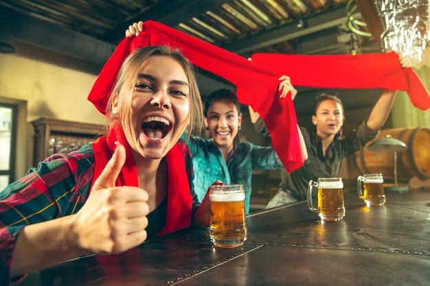 Deporte, gente, ocio, amistad, concepto de entretenimiento: felices fanáticas del fútbol femenino o buenos amigos jóvenes bebiendo cerveza, celebrando la victoria en el bar o pub. concepto de emociones positivas humanas
