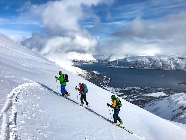Deporte de invierno, grupo caminando en la nieve, skitouring, fiordo de noruega, montaña