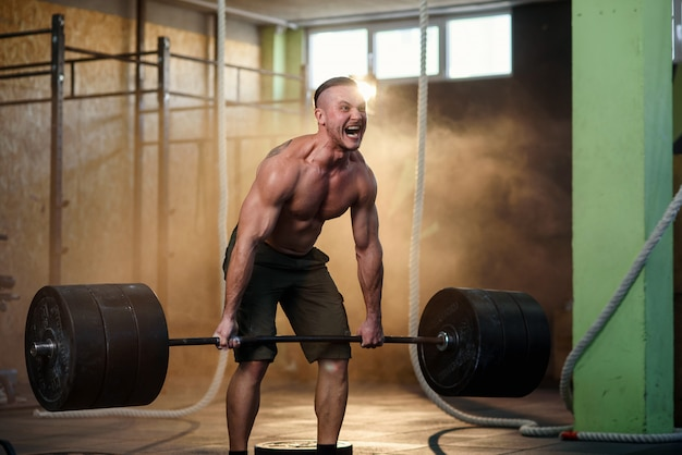 Deporte joven haciendo cuclillas con barra en el gimnasio.