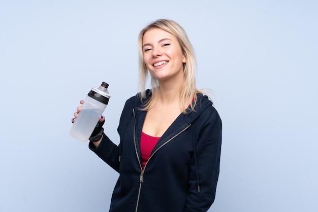 Deporte joven mujer rubia sobre pared azul aislada con botella de agua deportiva