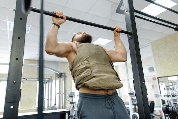 Deporte militar, musculoso hombre adulto barbudo caucásico haciendo ejercicios