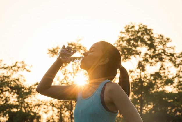 Deporte mujer agua potable durante la mañana para correr