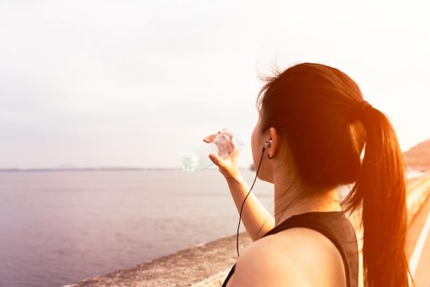 Deporte mujer de pie en la bahía y agua potable después de correr