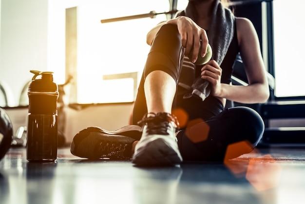 Deporte mujer sentada y descansando después de entrenamiento o ejercicio en gimnasio con proteína shak