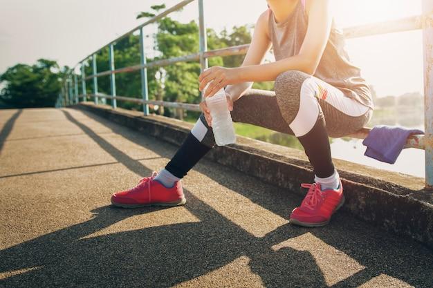 Deporte mujer sentada después de correr con la celebración de bebida de botella de agua