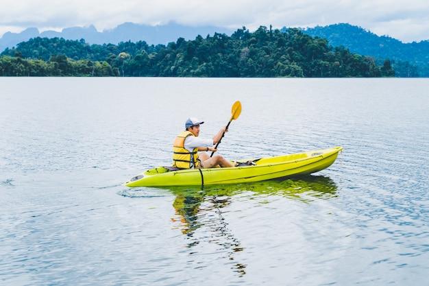 Deporte y recreación. joven disfruta de kayak de vacaciones en cheow lan lake, tailandia