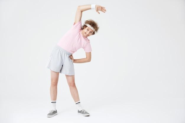 Deporte retro 70. hombre estirando los músculos de la espalda inclinándose hacia la izquierda