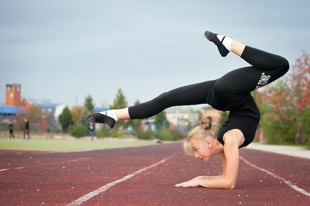 Deportes adolescente en el estadio realiza ejercicios gimnásticos