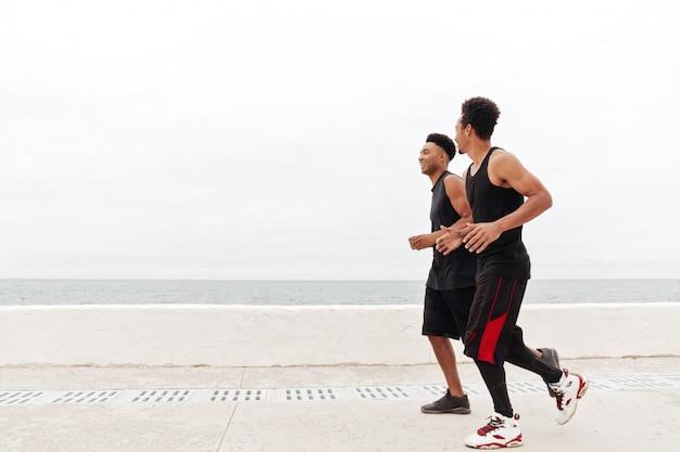 Deportes africanos hombres amigos corriendo al aire libre