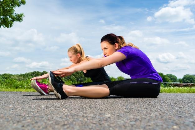Deportes al aire libre - mujeres jóvenes haciendo fitness en el parque